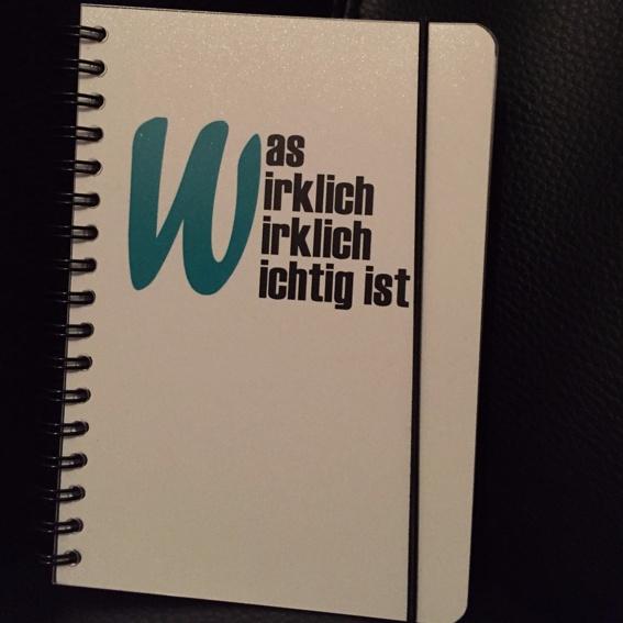 """Notizbuch mit Handsignation und der Aufschrift """"Was wirklich wirklich wichtig ist"""""""